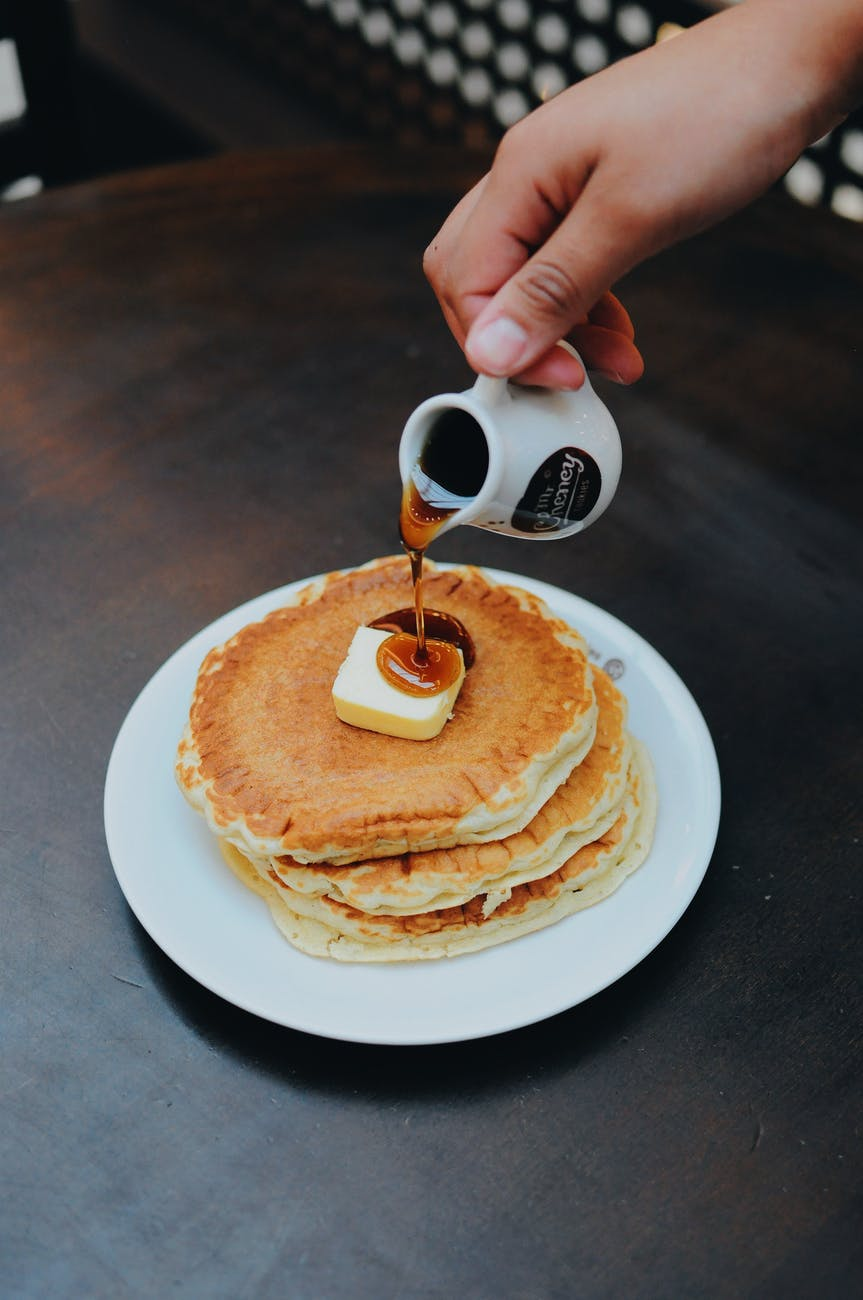 photo of a person pouring syrup on pancake